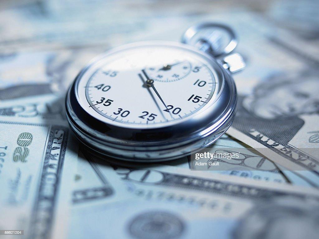 Close up of stopwatch on 20 dollar bills : Stock Photo