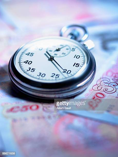 close up of stopwatch on 50 pound notes - fifty pound note stock pictures, royalty-free photos & images
