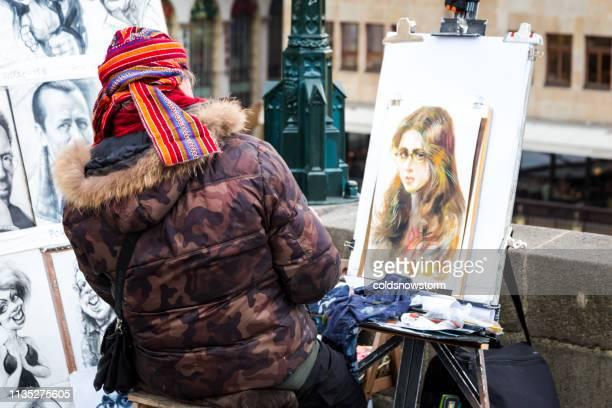 Close up of street artist painting portrait on Charles Bridge, Prague, Czech Republic