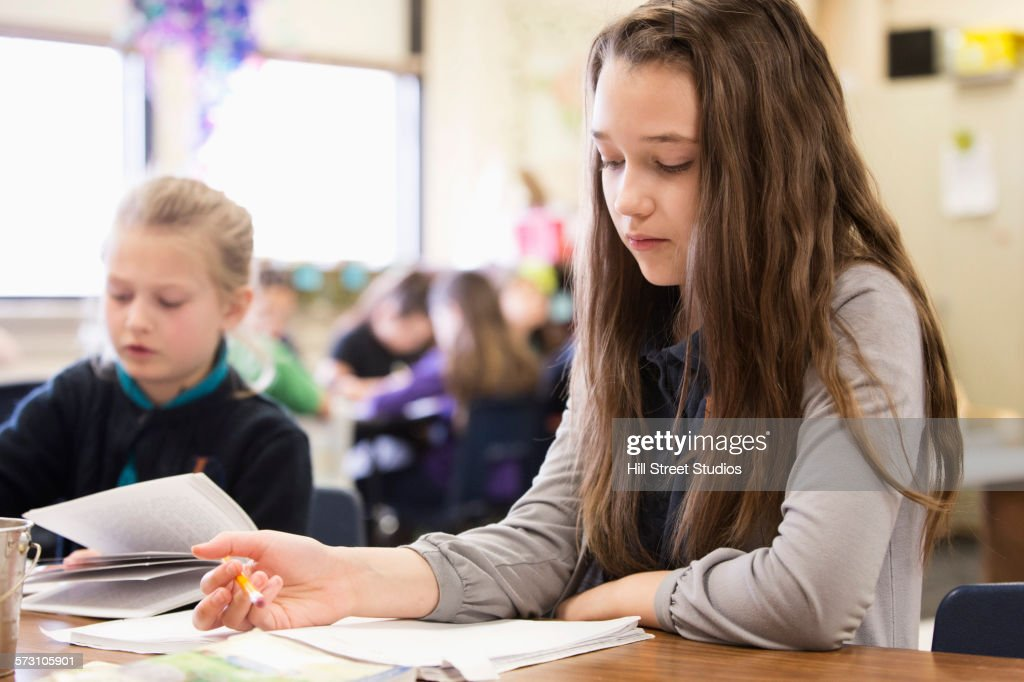 Close up of student reading in classroom : Stock Photo