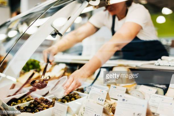 close up of supermarket clerk filling cup with olives - delicatessen stock pictures, royalty-free photos & images