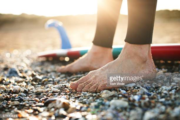 close up of surfers feet on the beach - pebble stock pictures, royalty-free photos & images