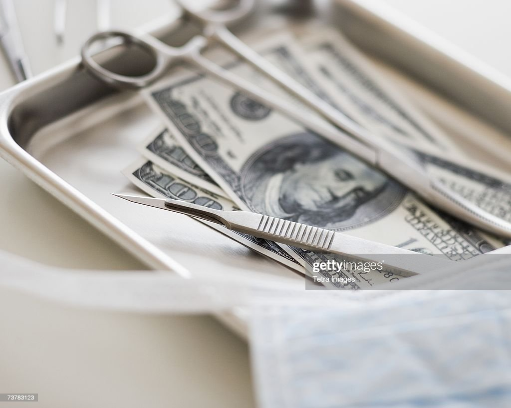 Close up of surgical tools and money : Stock Photo