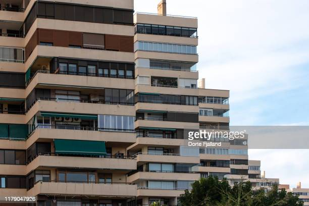close up of tall apartment complex with a bit of blue sky and white clouds to the right - dorte fjalland stock pictures, royalty-free photos & images