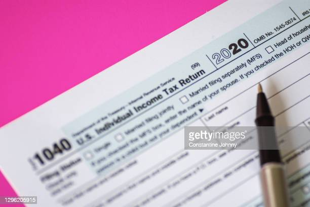 close up of tax form 1040 for year 2020 on pink background - tax stock pictures, royalty-free photos & images