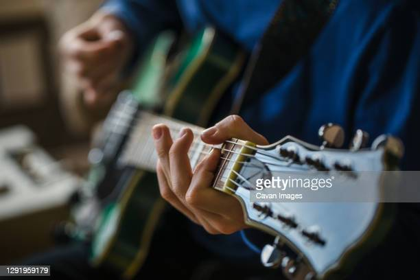close up of teen boy playing the guitar - 爪弾く ストックフォトと画像