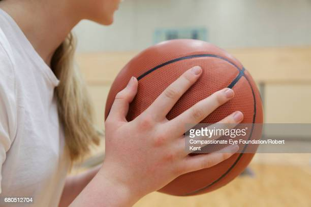 Close up of teenage basketball player in gym
