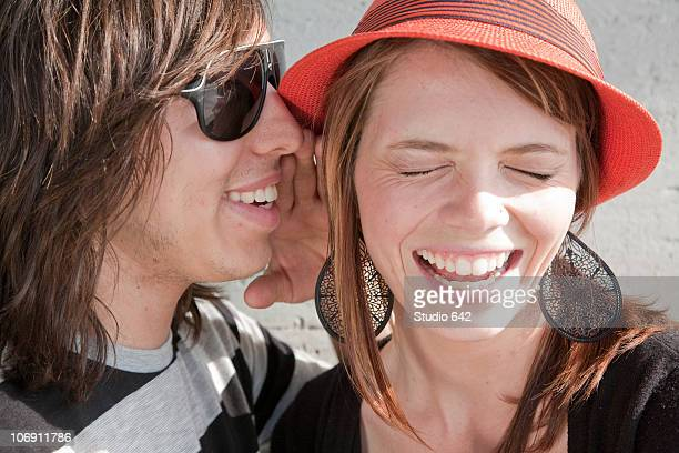 Close up of teenage boy whispering in smiling girl's ear