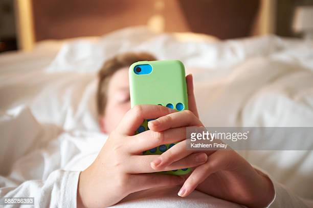 Close up of teenage boys hands holding smartphone on bed