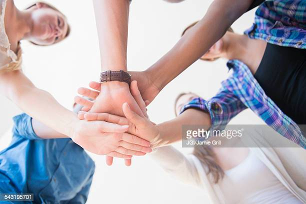 Close up of teenagers stacking hands in huddle