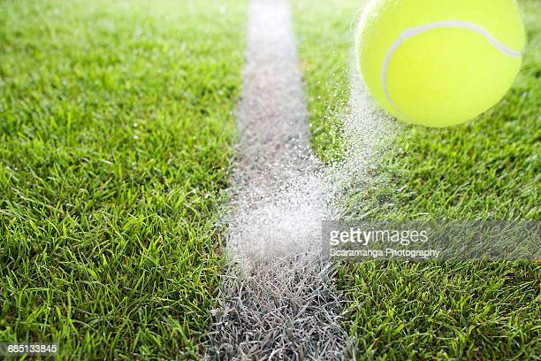 Close up of tennis ball hitting chalk line