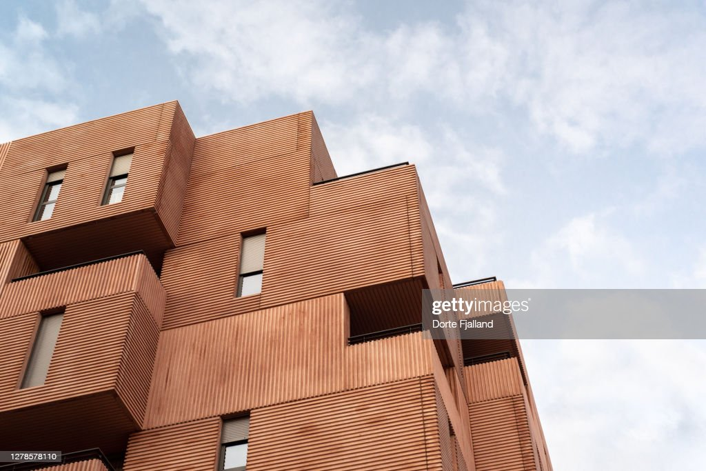 Close up of terracotta colored modern apartment building against a slightly cloudy blue sky : Foto de stock