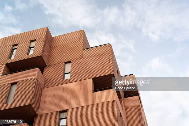 close up of terracotta colored modern apartment building against a slightly cloudy blue sky - dorte fjalland fotografías e imágenes de stock