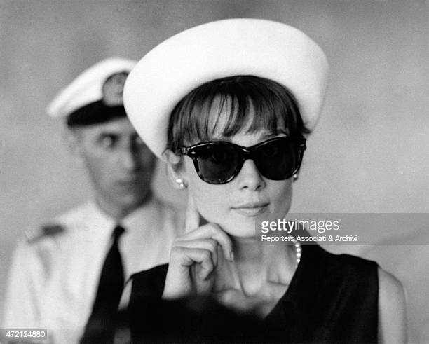 Close up of the British actress Audrey Hepburn wearing a big pair of sunglasses and a white hat at the airport at her backs stand a pilot in uniform...