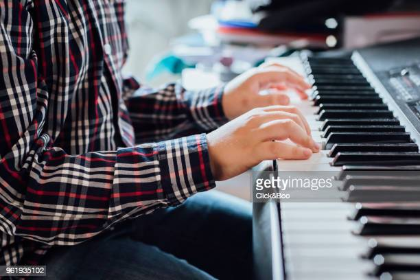 Close up of the hands of a boy playing the piano.