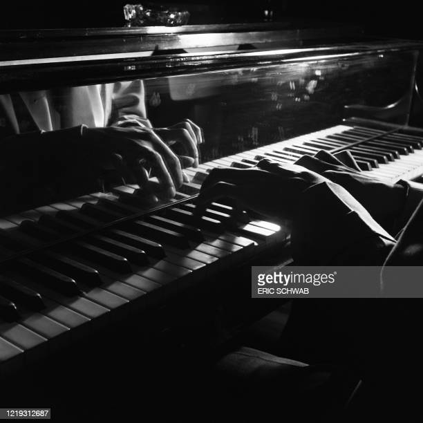 Close up of the hands of US pianist Pete Johnson playing on stage at the Café Society Downtown jazz night club, with US jazz drummer J.C. Heard and...