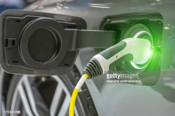 close up of the hybrid car electric charger station with power supply plugged into an electric car being charged. - electric car stock pictures, royalty-free photos & images