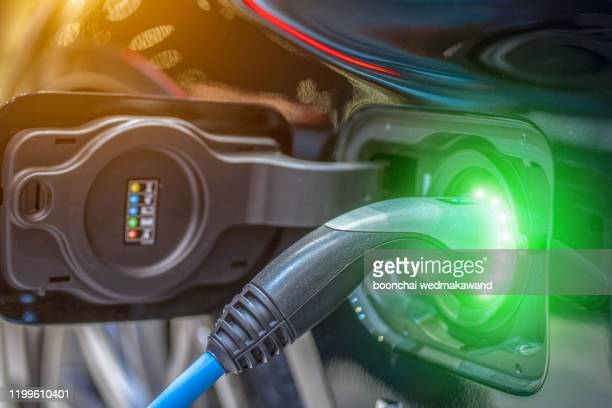 close up of the hybrid car electric charger station with power supply plugged into an electric car being charged - alternative fuel vehicle stock pictures, royalty-free photos & images