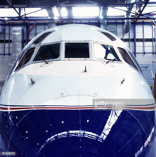 close up of the nose of an aircraft parked in a hanger
