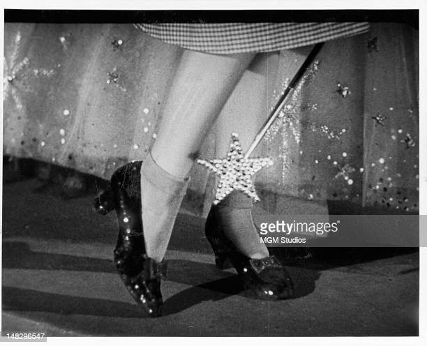 Close up of the ruby slippers on Judy Garland's feet with the tip of Glinda's wand in a scene from the film 'The Wizard Of Oz' 1939