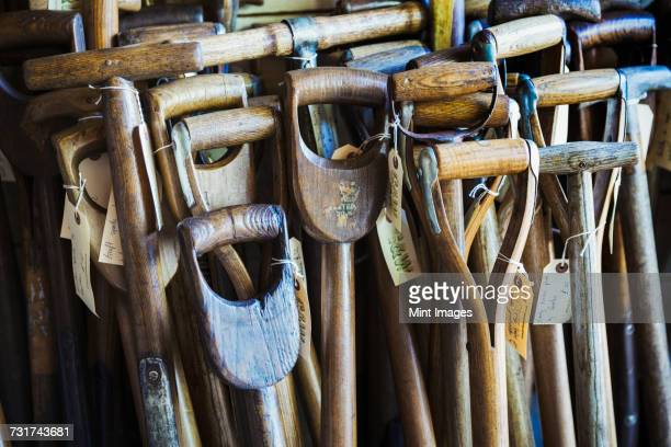 close up of the worn and weathered wooden handles of old traditional spades in a workshop with information labels attached. - large group of objects stock pictures, royalty-free photos & images