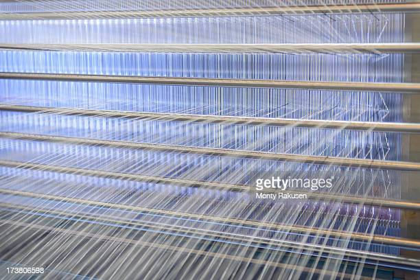 Close up of threads on industrial loom in textile mill