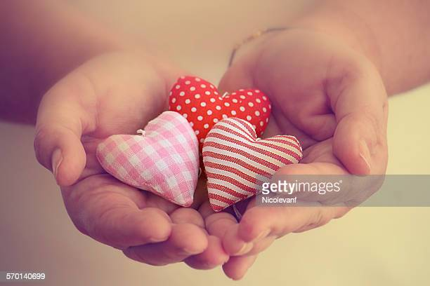 Close up of three handmade hearts in the palm of a woman's hands