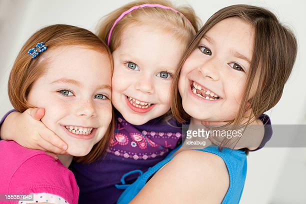 close up of three happy sisters hugging each other - hazel bond stock photos and pictures