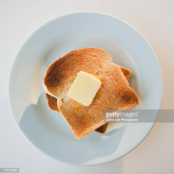Close up of toasts with butter on plate