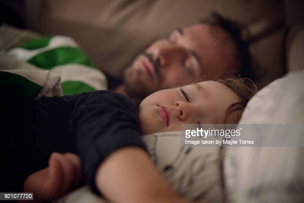 close up of toddler and dad taking a nap on the sofa - domingo fotografías e imágenes de stock