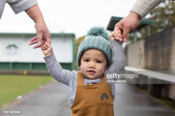 close up of toddler holding hand with parents - adoptie stockfoto's en -beelden