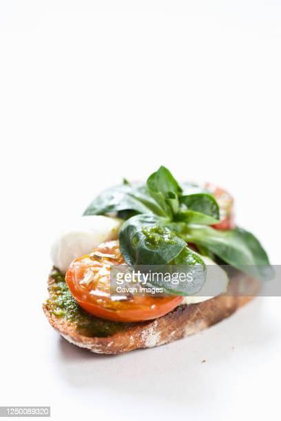 close up of tomato and mozzarella bruschetta on white background - pesto stock pictures, royalty-free photos & images