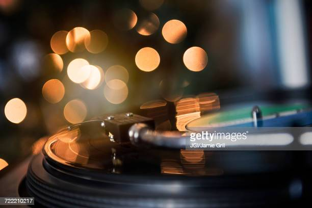 Close up of tonearm on spinning record player