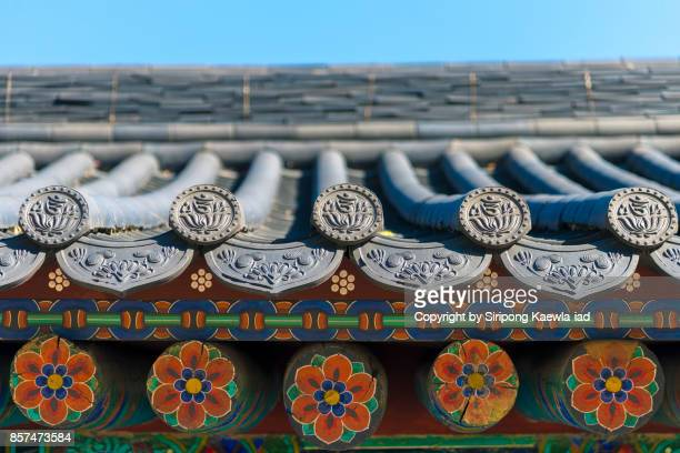 Close up of traditional Korean roof tiles and its painting wooden support in the bottom.