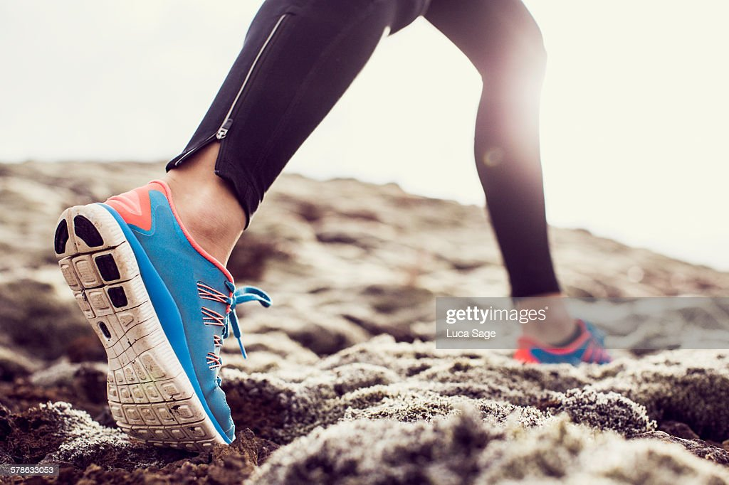 Close up of trainers running through mossy terrain : Stock Photo