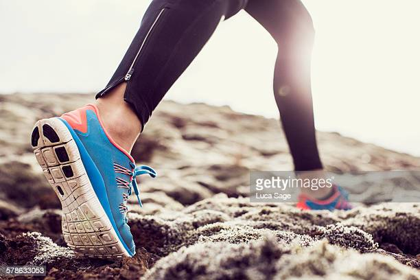 close up of trainers running through mossy terrain - blue shoe stock pictures, royalty-free photos & images