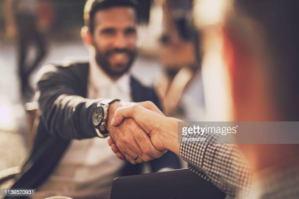 close up of two businessmen shaking hand in a city cafe. - fiducia foto e immagini stock