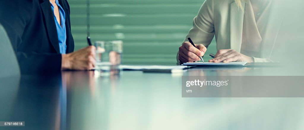 Close up of two businesswomen signing contracts at a conference : Stock Photo