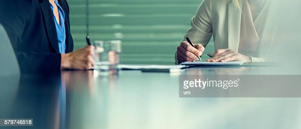 close up of two businesswomen signing contracts at a conference - tavolo da conferenza foto e immagini stock