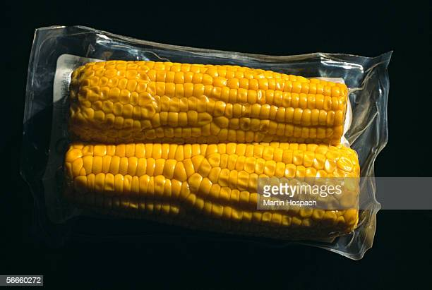 close up of two corncobs packed in plastic - airtight stock photos and pictures