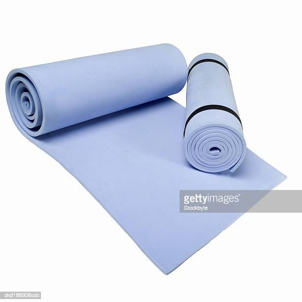 Close up of two exercise mats with one of the mats rolled up