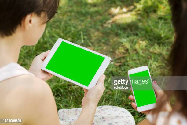 close up of two female friends using smart phone and digital tablet - chroma key foto e immagini stock