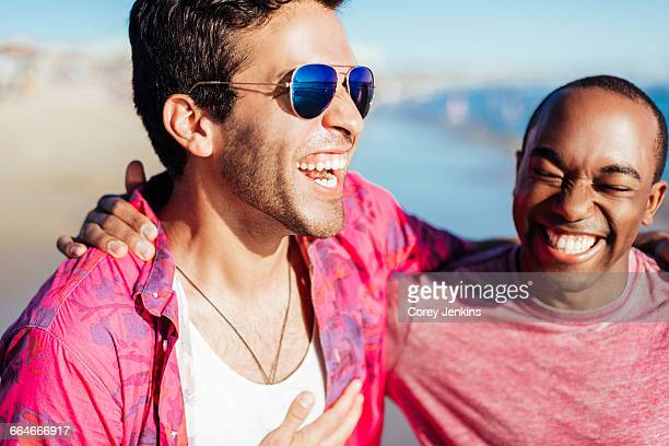 Close up of two male friends laughing on beach, Santa Monica, California, USA