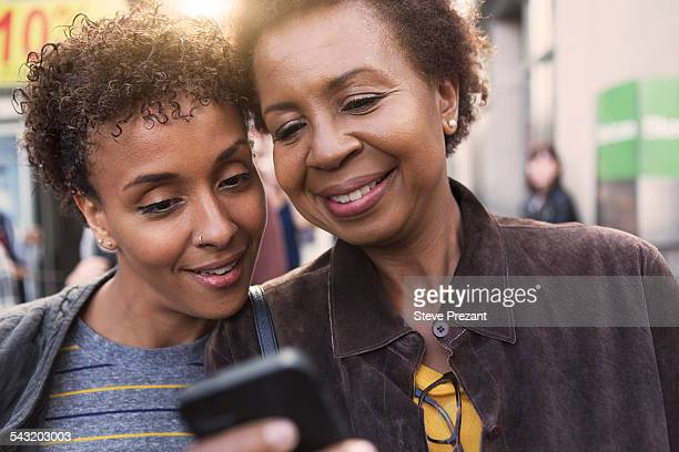 Close up of two mature female friends reading smartphone texts on street