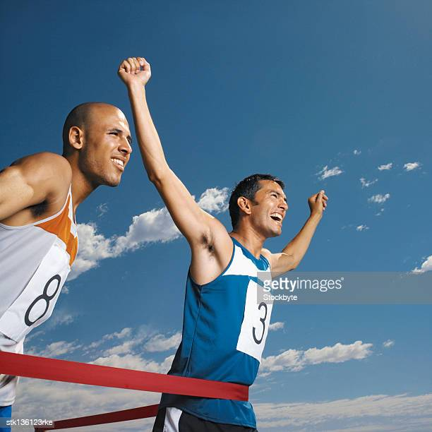 close up of two men running, reaching finish line
