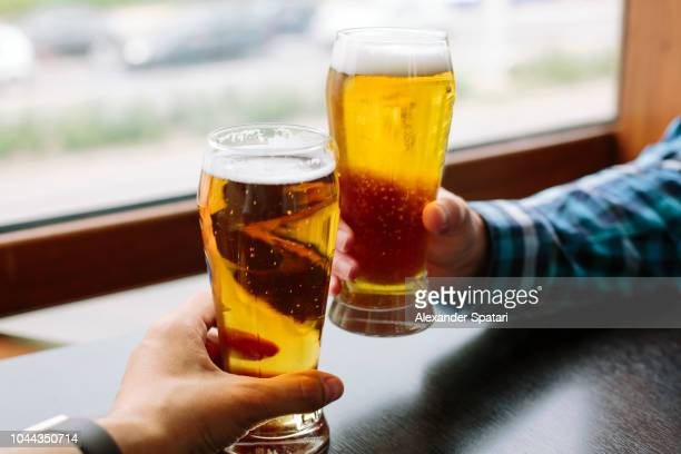 Close up of two men's hands holding beer glasses