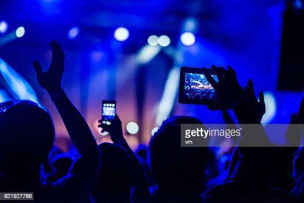 Close up of two people filming a concert