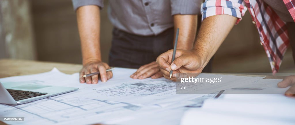 Close up of two people reviewing building blueprints : Stock Photo