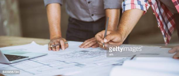 Close up of two people reviewing building blueprints