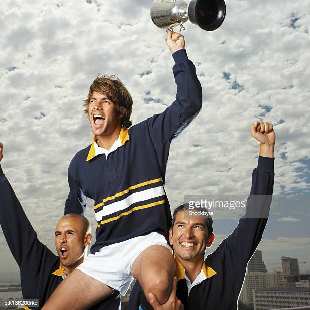 close up of two rugby players holding other player on their shoulders with the trophy